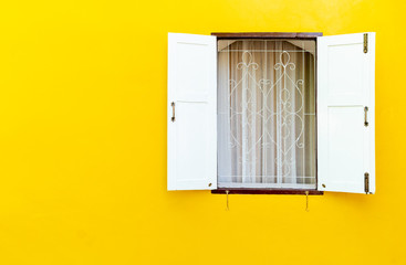 Wall Mural - The white wooden window was opened, where the windows were on the concrete walls of yellow. with blank copy space.