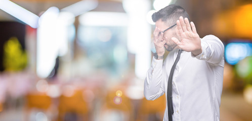 Young handsome business man wearing glasses over isolated background covering eyes with hands and doing stop gesture with sad and fear expression. Embarrassed and negative concept.