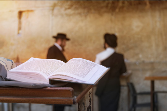 Jewish bible on table, wailing western wall, jerusalem, israel. book of the Torah-the Pentateuch of Moses is open on the prayer table on the background of praying Orthodox Jews