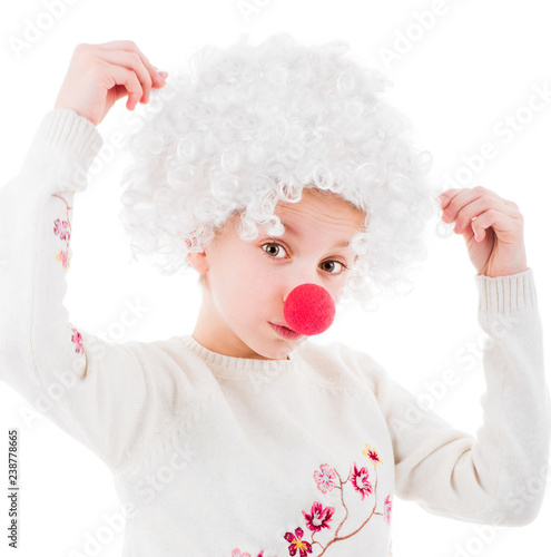 Lovely little girl in white voluminous clown wig and red nose posing