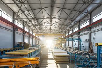 Worksop with machinery tools and equipment, conveyor line for production metal pipes and sandwich panels in factory interior