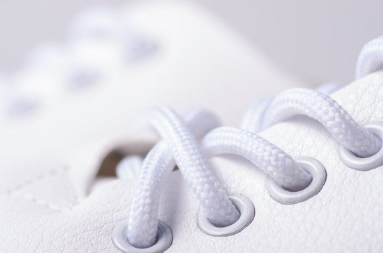 White leather sneakers shoes laces macro blur background