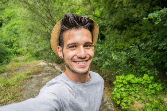 Handsome man smiling on the camera taking a selfie in a forest