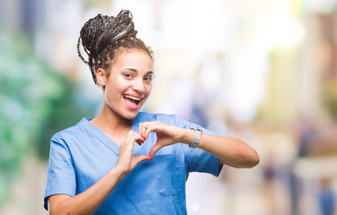 Young braided hair african american girl professional nurse over isolated background smiling in love showing heart symbol and shape with hands. Romantic concept.