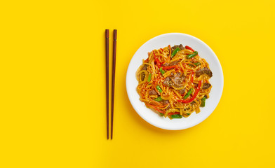 Stir fry noodles with beef and vegetables on a yellow background. Flat lay with top view and copy space