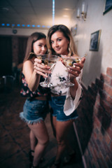Girls with glasses of white wine in a nightclub