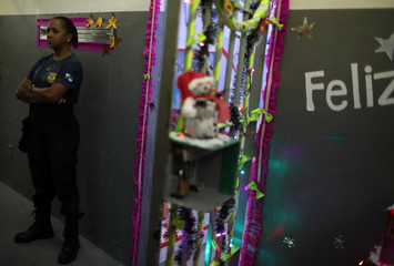 """A guard stands next to a decorated cell during a Christmas event """"Bright prison cell"""" at the Nelson Hungria prison in Rio de Janeiro"""
