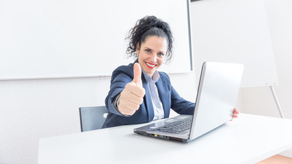 Portrait of a normal business woman doing thumb up sign in a office desk. With copy space. Dressing professionally smiling & looking at the camera. Black hair and blue eyes