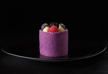 Purple berry mousse cake with blackberry, blueberry and raspberry on black plate