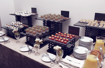 Assortment of snacks on banquet table, toned