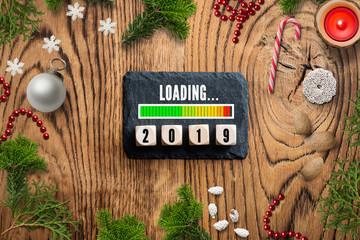Schiefertafel mit Ladebalken für 2019 und weihnachtlicher Dekoration auf rustikalem Holzuntergrund