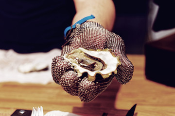 Chef is shoving open oyster, toned