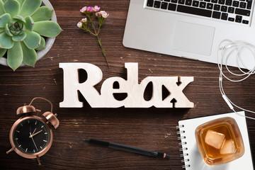 """Wort """"relax"""" auf Holzuntergrund und Bürodekoration"""