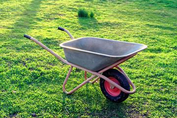 Empty wheel barrow in garden, toned