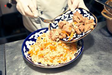 Chef is serving pilaf in restaurant kitchen