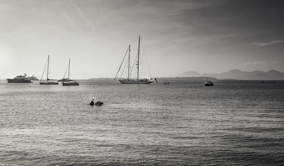 Black and white picture of the yachts and sailboats at anchor in Golfe Juan at the French beach resort of Juan-les-Pins with the island Ile Sainte-Marguerite in the background