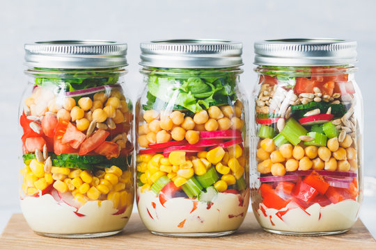 Glass jars with layering various vegan salads for healthy lunch. The concept of fitness and vegetarian food.