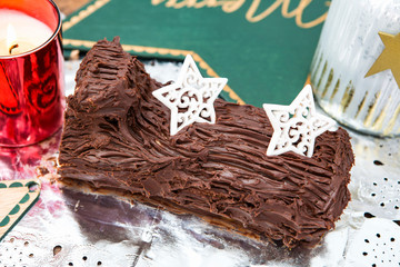 postre de tronco de Navidad cubierto de chocolate con dos estrellas blancas de adorno.