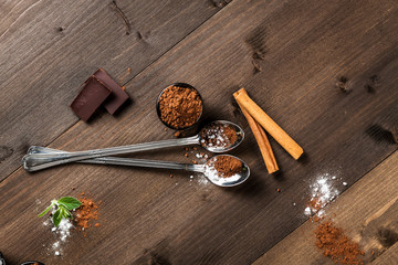 Long spoons on dark wood, cocoa and chocolate composition