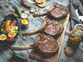 Grilled lamb, beef meat chops with vegetables on a serving board. Rustic food concept