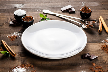 Empty white plate on dark wood, chocolate composition, angle view