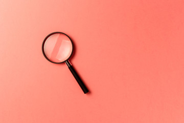 Magnifying glass on coral background. Top view. Flat lay. Copy space. New minimal creative concept. Living Coral color of the Year 2019
