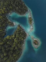 Aerial of a house on an islet surrounded by water and trees
