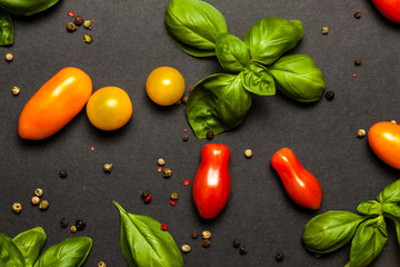 Basil, pepper and cherry tomatoes composition, on black background