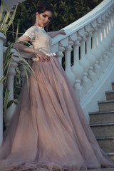 Beautiful lady with perfect make up in luxurious ballroom dress with tulle skirt and lacy top standing on stairs leaning on baluster railing. Vintage style