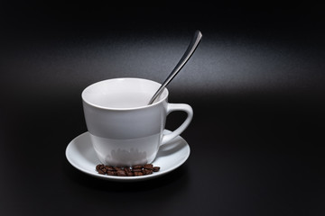 White cup, saucer and spoon on a black background