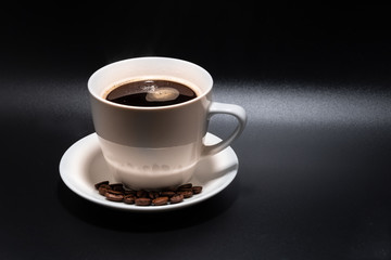 White cup and saucer with coffee on a black background