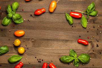 Basil, pepper and cherry tomatoes circular frame with copy space, on dark wooden table