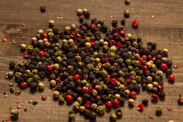 Mixed colors of pepper grains on dark wood