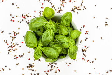 Bowl full of basil surrounded with pepper seeds on with white background