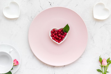Simple color table setting for celebration with wineberry, white plates and wineberry on white table background top view