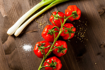 Red cherry tomatoes and green onion isolated on wooden cutting board
