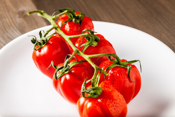 Red fresh cherry tomatoes on a white plate isolated on a wooden cutting board