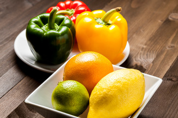 Citrus fruit and bell peppers in a white square bowls on a wooden table