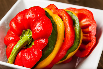 Fresh vibrant bell pepper slices in a white square bowl isolated on wooden surface