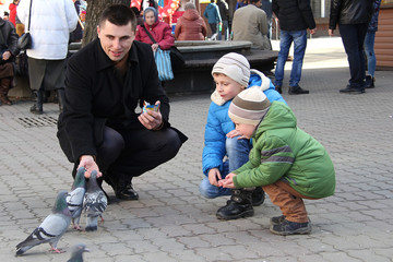Children in the city square feed the pigeons