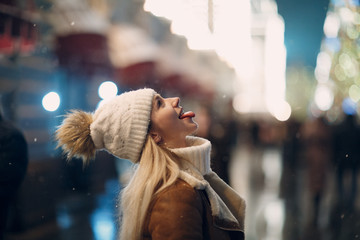 Young woman catches snowflakes by mouth