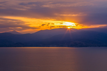 soft focus beautiful sunset scenic view in calm sea bay surrounded mountain unfocused silhouettes landscape with sun light and rays from above range top