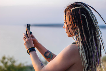 young beautiful hippie woman with dreadlocks uses smartphone, takes pictures of nature and takes a selfie at sunset