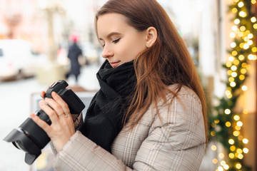 Photographer girl walk in the street and take photos in camera with happy face. Wear black scarf. Winter, autumn outfit.
