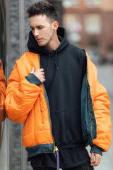 Fashionable man stand on the street near buildings. Wear orange jacket and all black. Winter, autumn outfit. Jacket with blouse and black sneakers.