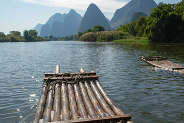Keuken foto achterwand Guilin Front of bamboo raft in foreground on Yulong River, Yangshuo, China. Limestone cliffs in silhouette along edge of river.