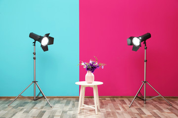 Professional lighting equipment and vase with flowers on table near wall in photo studio