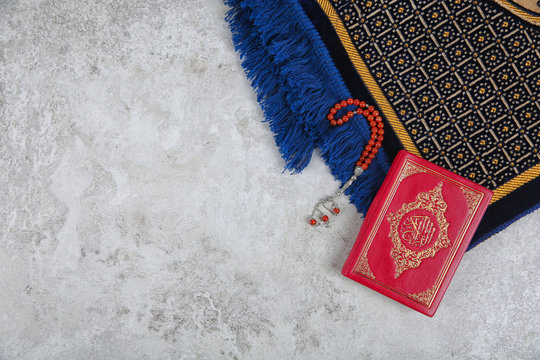 Muslim prayer beads, Quran, rug and space for text on grey background, top view