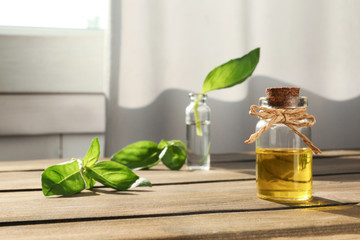 Bottle of essential basil oil on table against blurred background. Space for text