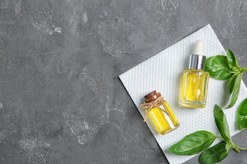 Bottles of essential basil oil, fresh leaves and space for text on grey background, top view